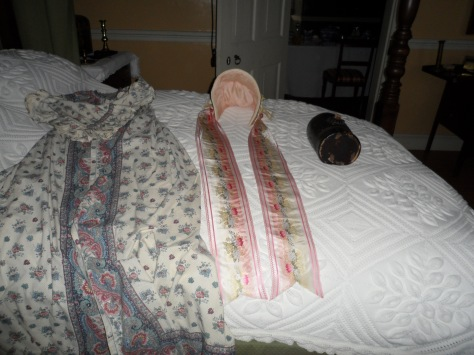 A pretty pink bonnet.  I was told that a bonnet on the bed was good luck but a top hat was bad.  I can't find anything to verify that.